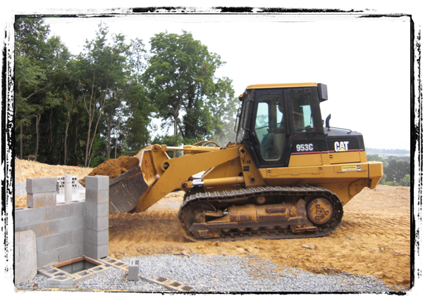 Image: Bulldozer moving dirt to install septic tank.